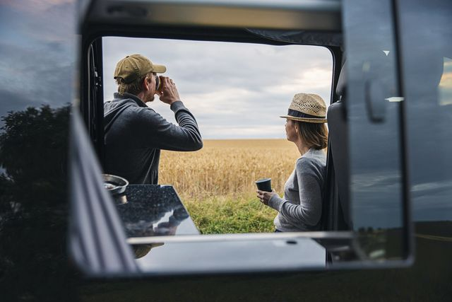 the camper is parked up in the countryside, next to a wheat field