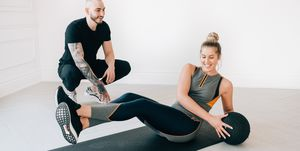 Fitness instructor observing woman doing Russian twist with medicine ball in studio