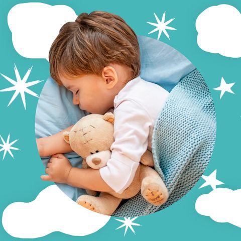 small boy lying in bed cuddling a teddy bear