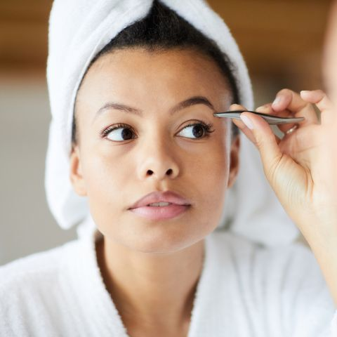 head and shoulders portrait of  beautiful mixed race woman plucking eyebrows looking in mirror during morning routine, copy space