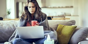 Sick woman sitting on sofa covered in blanket with cup of tea and laptop