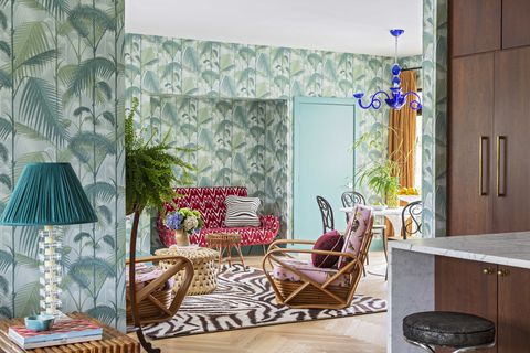 living room, with red sitting couch, palm tree wallpaper and large zebra area rug