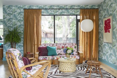 living room with zebra area rug, palm wallpaper, orange curtains on black curtain rods, pink tropical couch