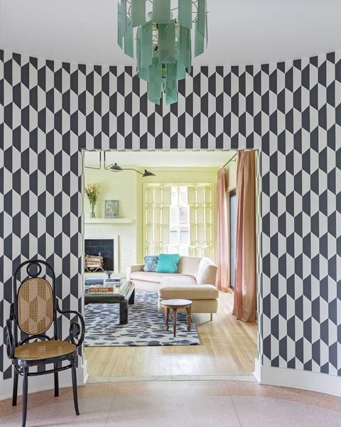 entryway into house, black and white geometric wallpaper, black and brown chair