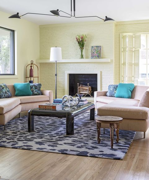 sitting room with yellow painted brick fireplace, pink couch with large black coffee table and coffee table books, leopard print area rug