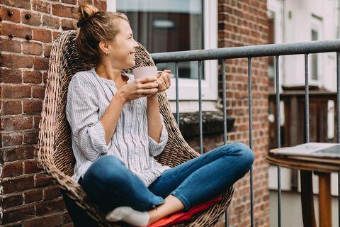 Vrouw drinkt koffie op balkon