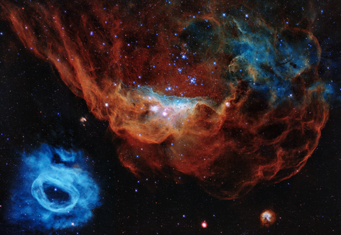 a giant red nebula with sparkling stars next to a smaller blue nebula in the bottom left corner