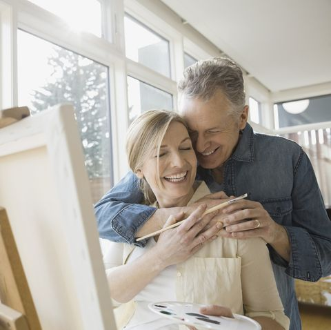 winter date ideas -Hugging couple painting at easel in living room