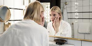 Vrouw bekijkt gezicht in spiegel