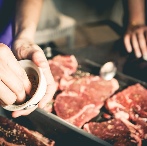 Human hand is preparing BBQ steak for party.