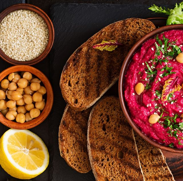 lemon, chickpeas and a bowl of hummus on a plate with toasted bread