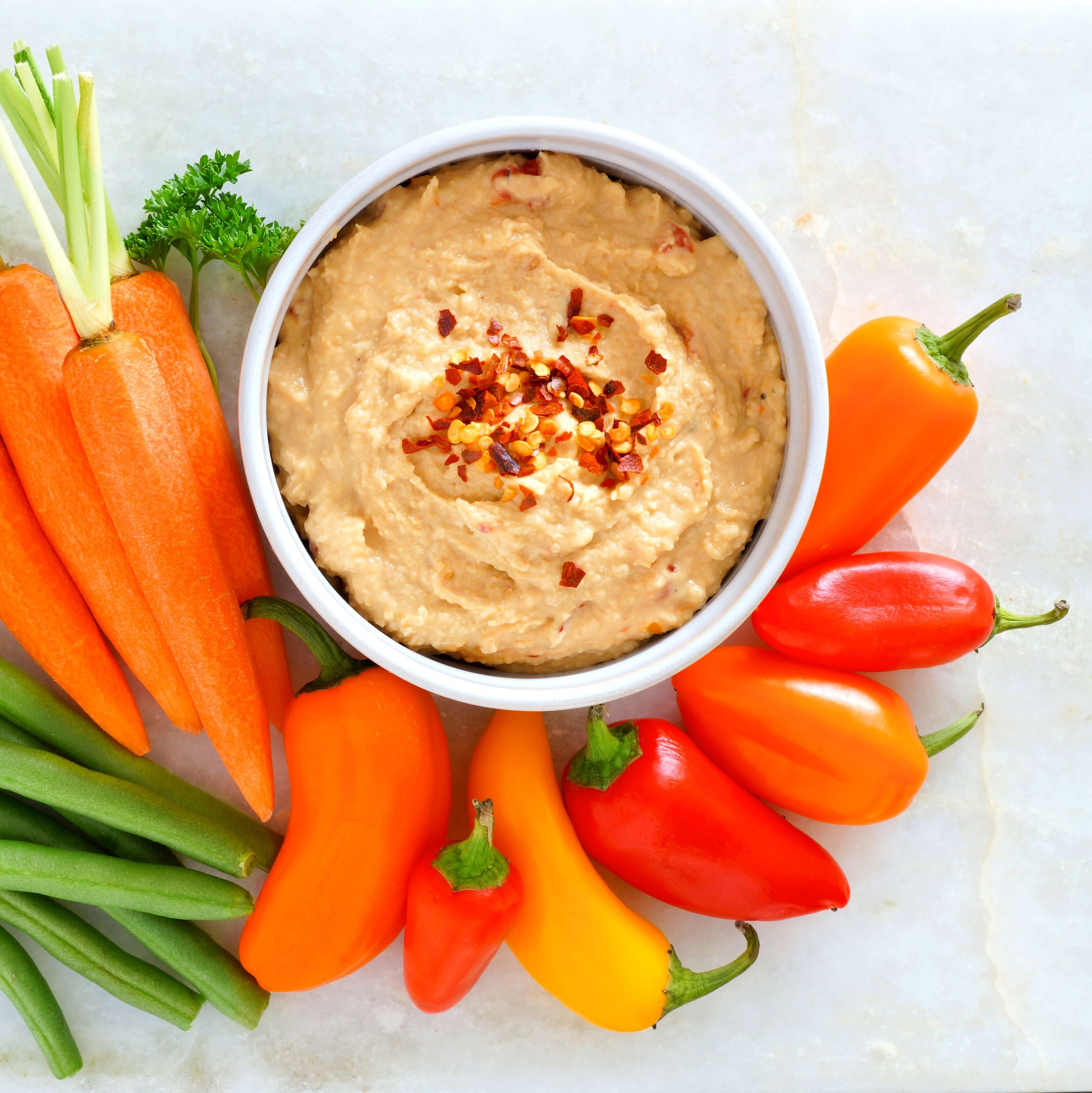 Hummus with fresh vegetables, above view on white marble