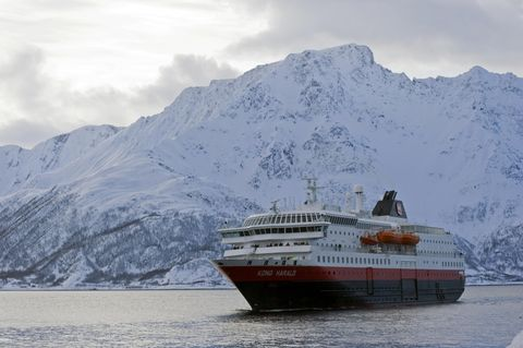 Hurtigruten cruise ship, MS Kong Harald, in front of a wintery fjord landscape, Oeksfjord, Finnmark, Norway