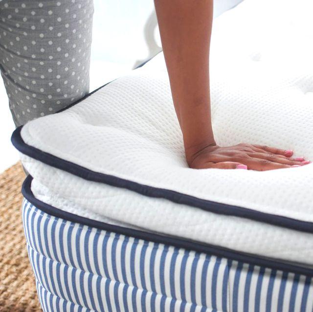 hand pushing down on hybrid mattress