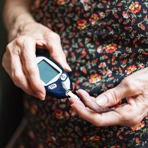 old lady tracking her glucose levels health concept