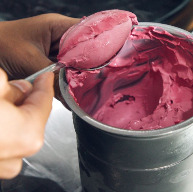 scooping homemade raspberry ice cream out of stainless steel bowl