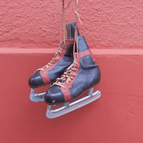 Ice skates hanging against red wall