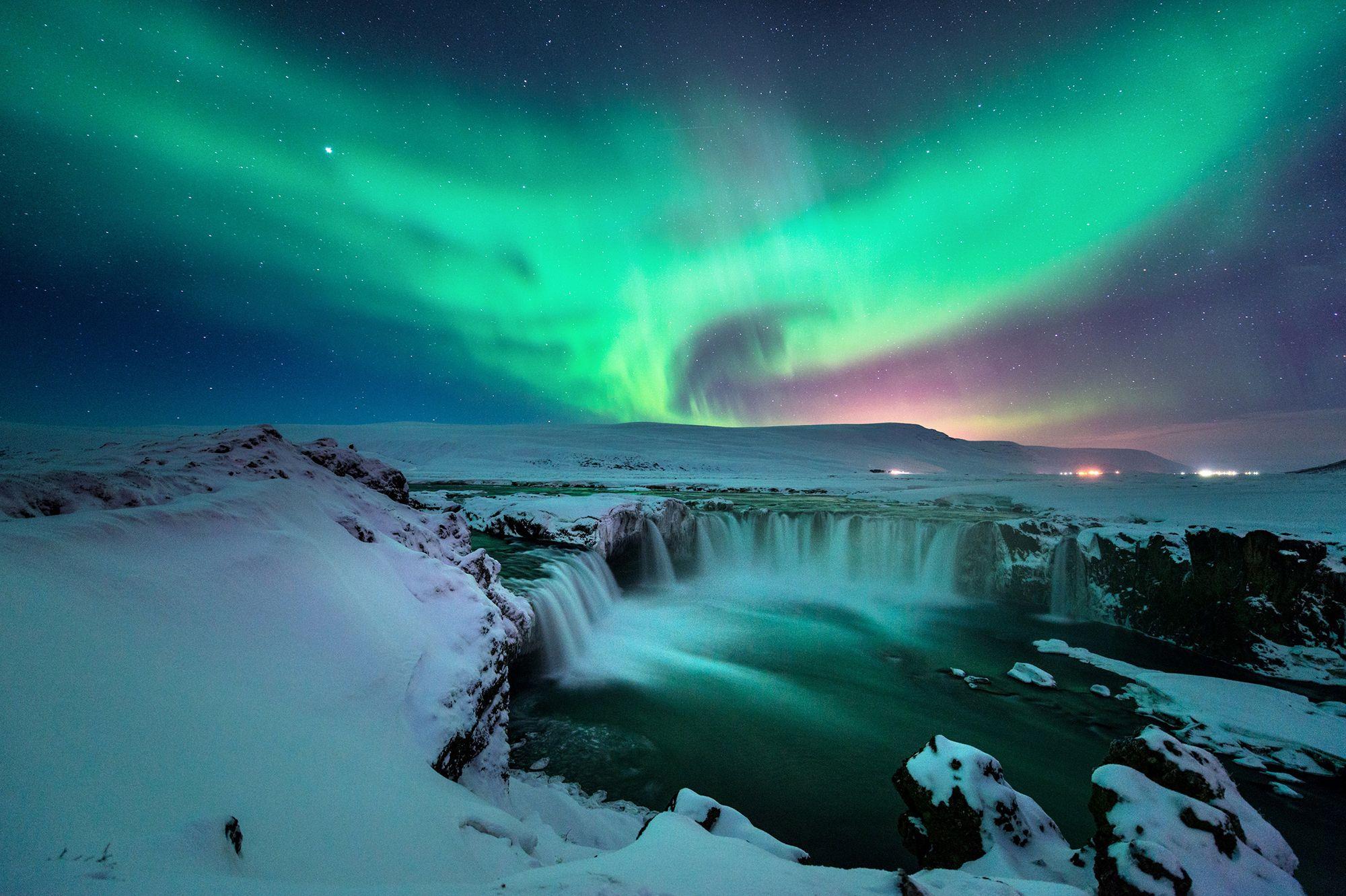 A stunning aurora shape like phoenix bird appears above the landscape of Godafoss water fall in winter Iceland