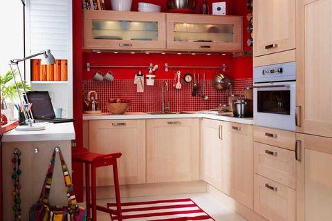 cocina con paredes rojas y muebles de madera