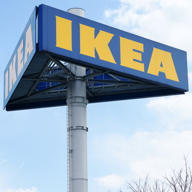 graz, austria   march 26, 2011 large ikea logo on pole in graz clouded sky in background tree is partly visible in lower part of image ikea is producer of low price furniture located south of stockholm in sweden with branches all over the world