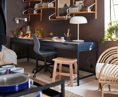Mesa de escritorio alargada en color azul oscura con silla giratoria