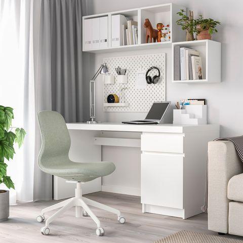 Mesa de escritorio blanca con silla giratoria tapizada con tela verde