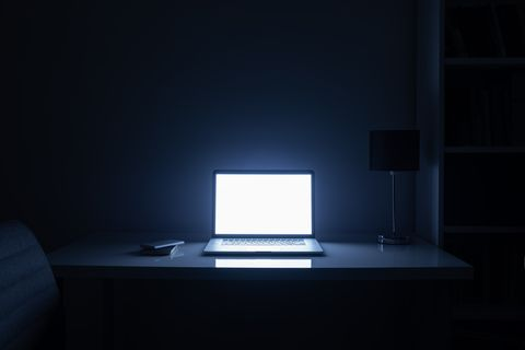 illuminated laptop on table at home