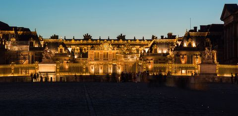 Illuminated Palace Of Versailles Against Sky At Dusk