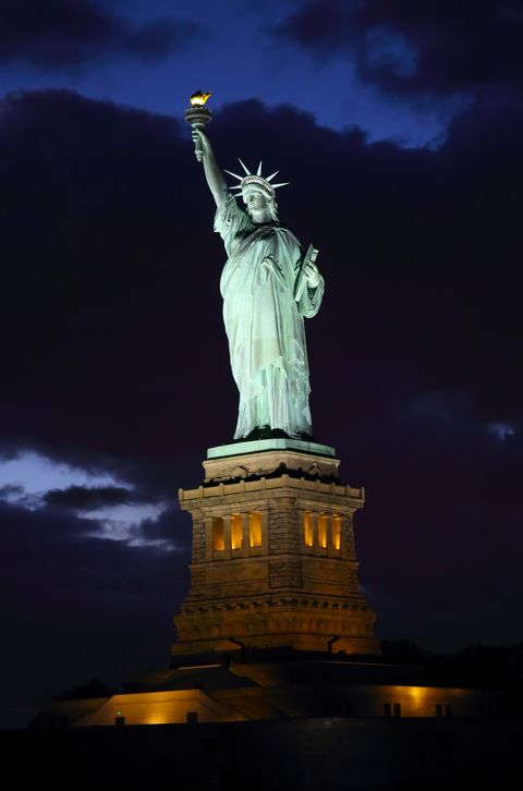 illuminated shot of statue of liberty at dusk