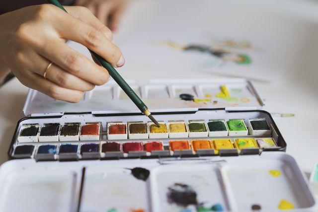illustrator painting at work desk, close up
