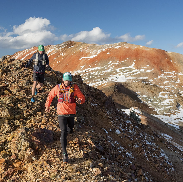 two people running on a rocky ridge