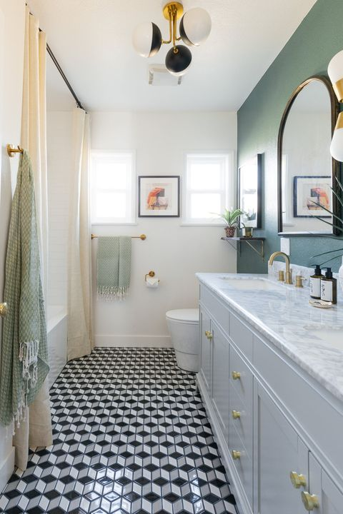 remodeled bathroom with white marble countertops and dark green wall paint