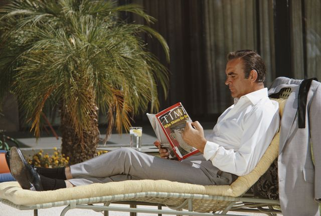 scottish actor sean connery relaxes on the set of the james bond film 'diamonds are forever', usa, may 1971 he is reading the 12th april 1971 edition of 'time' magazine, with lieutenant william calley jr on the cover photo by anwar husseingetty images
