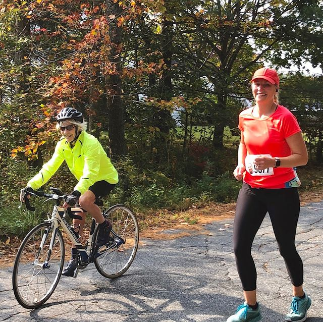 erika sahlman running alongside joan benoit samuelson on a bike