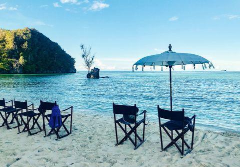 sundowners on the beach of a deserted island, raja ampat archipelago, indonesia