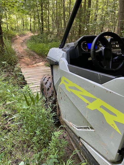 Polaris rzr trail on a narrow wooden bridge