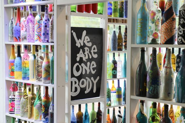 """a community in williamsburg, virginia creates a """"stay at home"""" art installation built by resident painted wine bottles"""