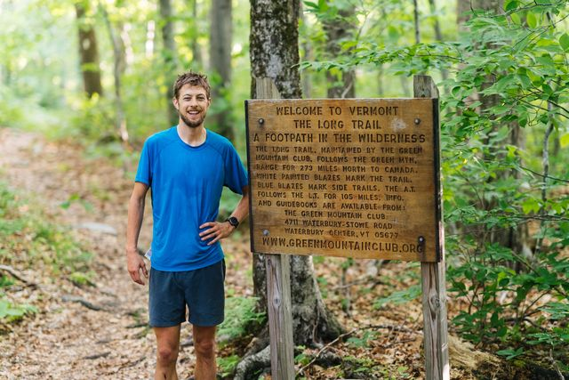 joe mcconaughy stands next to the long trail sign after capturing the unsupported fkt on june 15