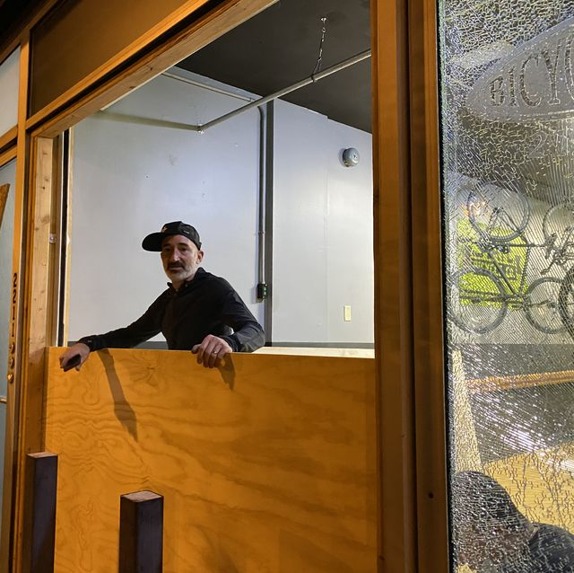 bicycle therapy owner lee rogers stands in the broken window of his storefront
