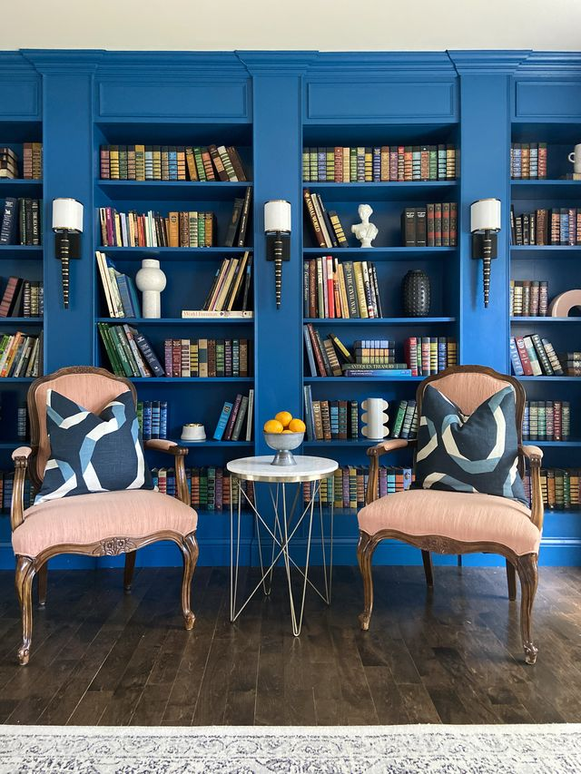 blue library, blue bookcases with books, red reading chairs, black and white sconces