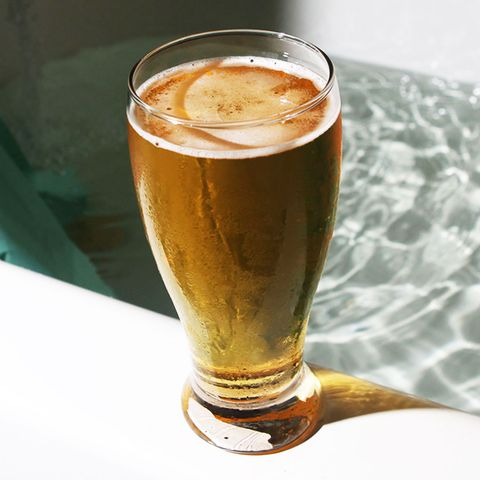beer on the edge of a bathtub in a tall glass
