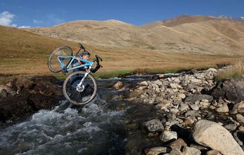 shannon galpin crossing a river with her bike