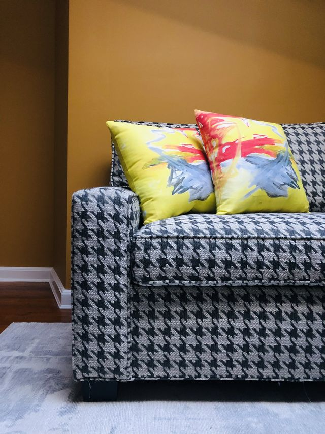 abstract painting pillows on houndstooth sofa