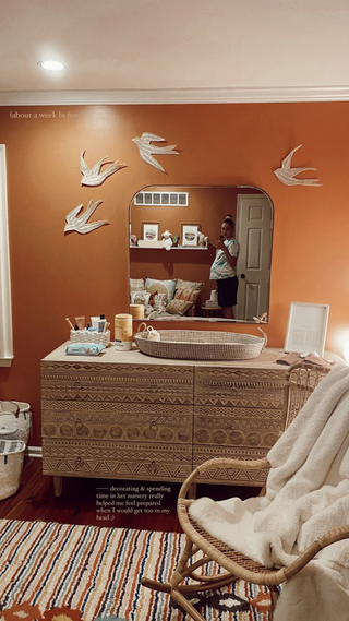 gigi takes a mirror selfie wearing baggy shorts and a bluewhite tie dye t shirt the nursery walls are orange with white bird decals over the mirror the light wooden dresser is carved with patterns
