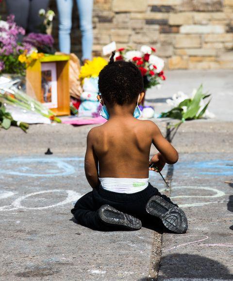 a little boy kneels in minneapolis, minnesota, near where george floyd was murdered