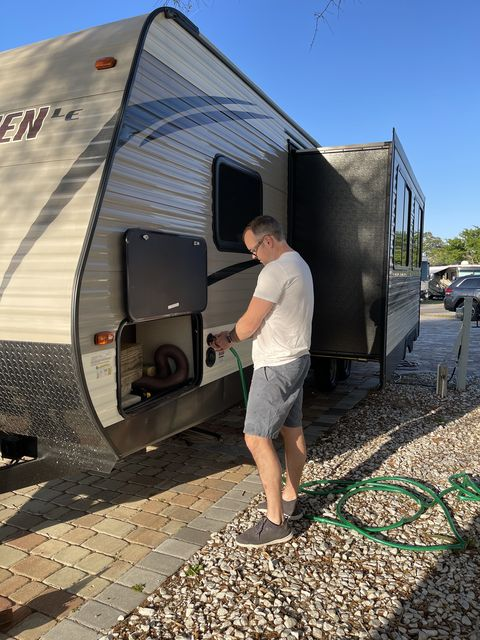 extremely handsome man hooking up water hose to rv trailer
