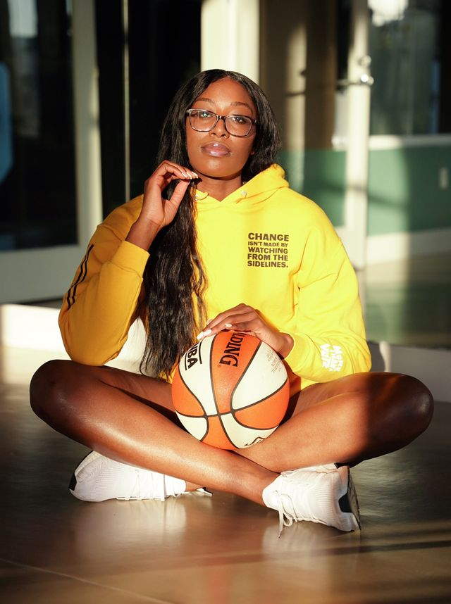 chiney ogwumike sits cross legged on the floor with a basketball in her lap