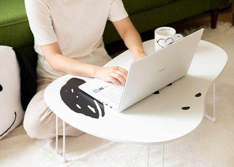 一個人坐在地板上並在黑白史努比折疊桌上用電腦