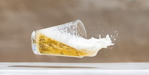 Impact of a glass  with beer that falls down on the soil.