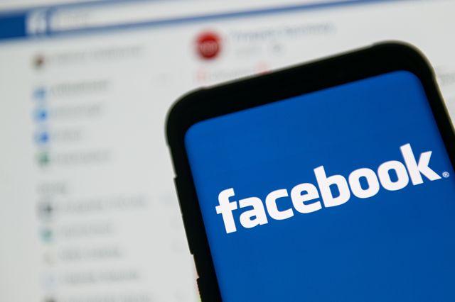facebook logo on smartphone in front of facebook desktop site